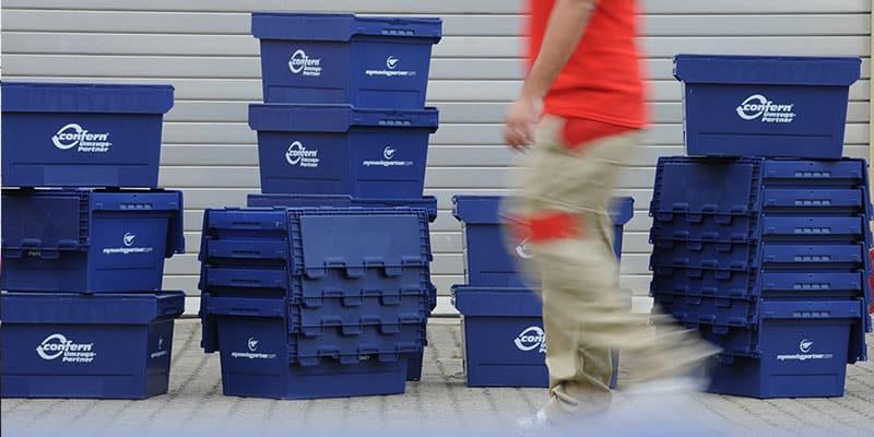 Unser Mitarbeiter stapelt die umweltfreundlichen confern-Boxen, eine Alternative zum Umzugskarton.